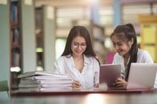 Duas meninas fazem pesquisa em biblioteca | foto: Designed by jcomp / Freepik