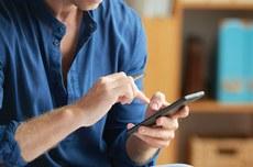 Pessoa acessa a transmissão da reunião pelo celular | Foto: Pressfoto by Freepik