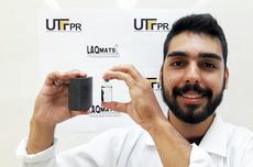 """Aluno Brayan Medina, com frasco contendo água e partículas magnéticas de magnetita finamente particuladas (à direita) sendo atraídas pelo magneto de neodímio (à esquerda). Esse comportamento comprova a capacidade de """"locomoção"""" das nanopartículas em água"""