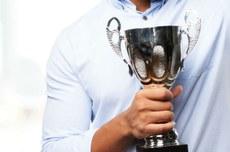 Mão segurando um troféu | Foto: Designed by kues1 / Freepik