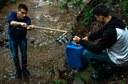 Dois alunos coletam amostra de água em rio na cidade de Toledo (Foto: Reprodução/Casa de Notícias)