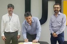 Reitor Luiz Alberto Pilatti assina a primeira revalidação de diploma da plataforma Carolina Bori acompanhado do pró-reitor de Graduação, Luís Mauricio Resende (direita), e do gestor institucional responsável pela revalidação dos diplomas de graduação na UTFPR, Paulo Silveira (esquerda).