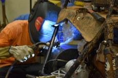 Aluno faz manutenção em protótipo de veículo no Câmpus Curitiba (Foto: Decom)
