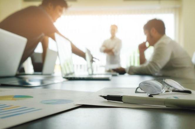 mesa de reunião com homens ao fundo